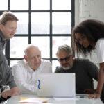 Equipe de 4 pessoas conversando em frente ao computador. Imagem simboliza o debate sobre ferramentas de gestão industrial.