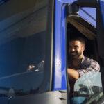 Motorista feliz dentro de caminhão. Imagem simboliza o modelo Cross Docking.