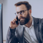 Profissional olhando para o computador e falando no telefone. Imagem simboliza que está trabalhando com PLM e ERP.