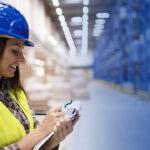 Profissional mulher anotando informações em um estoque. Imagem simboliza a atuação com a Supply Chain.