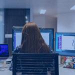 Mulher trabalhando em frente a 3 máquinas. Imagem simboliza o trabalho com o low-code/no-code.