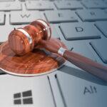 Martelo de juiz em cima de teclado. Imagem representa os benefícios em usar o ERP no Compliance Fiscal.