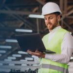 Homem mexendo no computador dentro de uma fábrica. Imagem simboliza o uso do just in time nas indústrias.