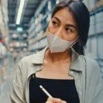 Mulher olhando estoque em fábrica. Imagem simboliza que está planejando o estoque mínimo.