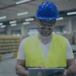 Homem segurando tablet dentro de indústria. Imagem simboliza que está trabalhando com a produção puxada ou empurrada.